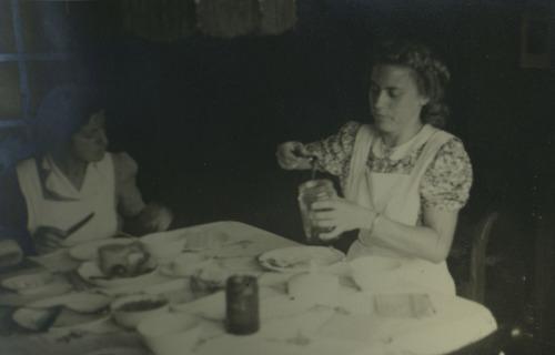 Twee verzorgsters van het babyhuis smeren brood.