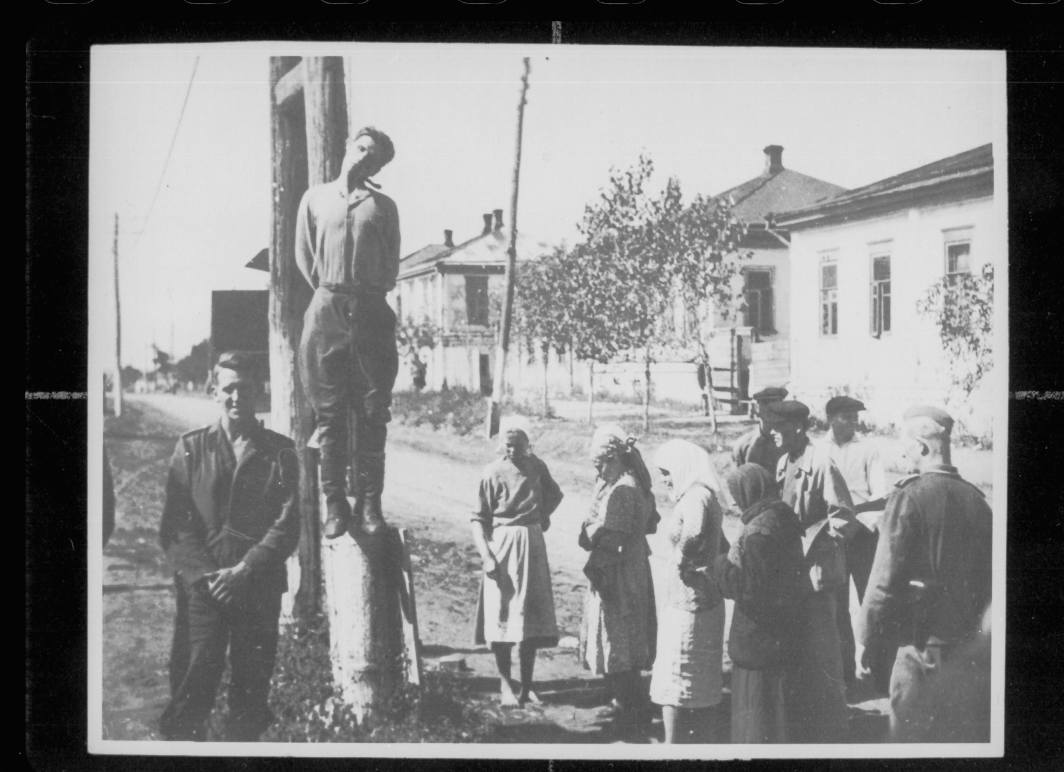 Nederlandse NSKK ers aan het Oostfront poseren voor een opgehangen partizaan