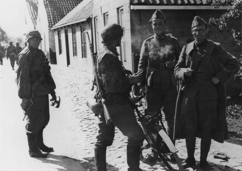 Waffen-SS'er van het Regiment Deutschland praat met twee ontwapende Nederlandse militairen op 17 mei 1940 in Kapelle