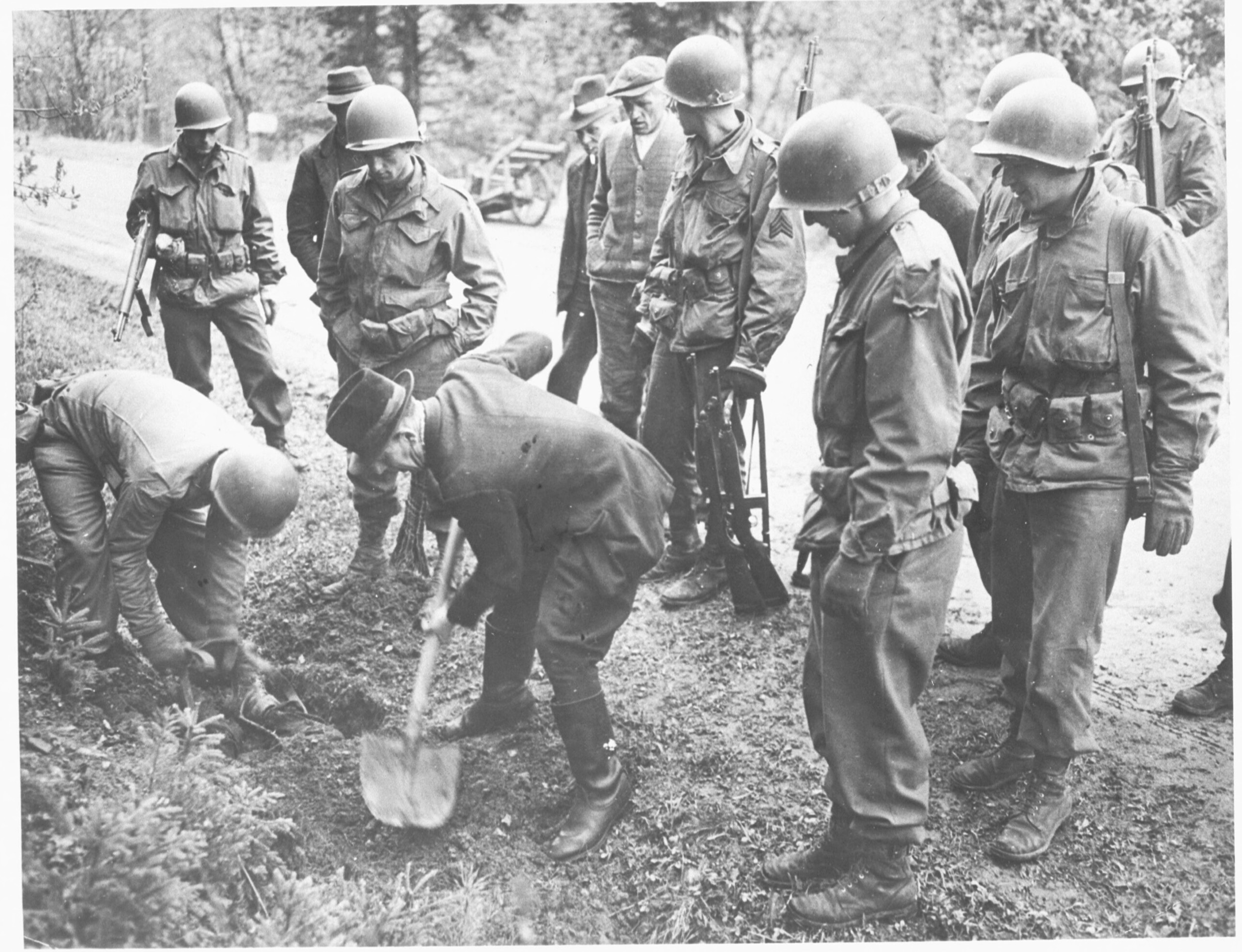 Amerikaanse militairen dwingen Duitse burgers om slachtoffers van een dodenmars op te graven bij Kamp Flossenbürg