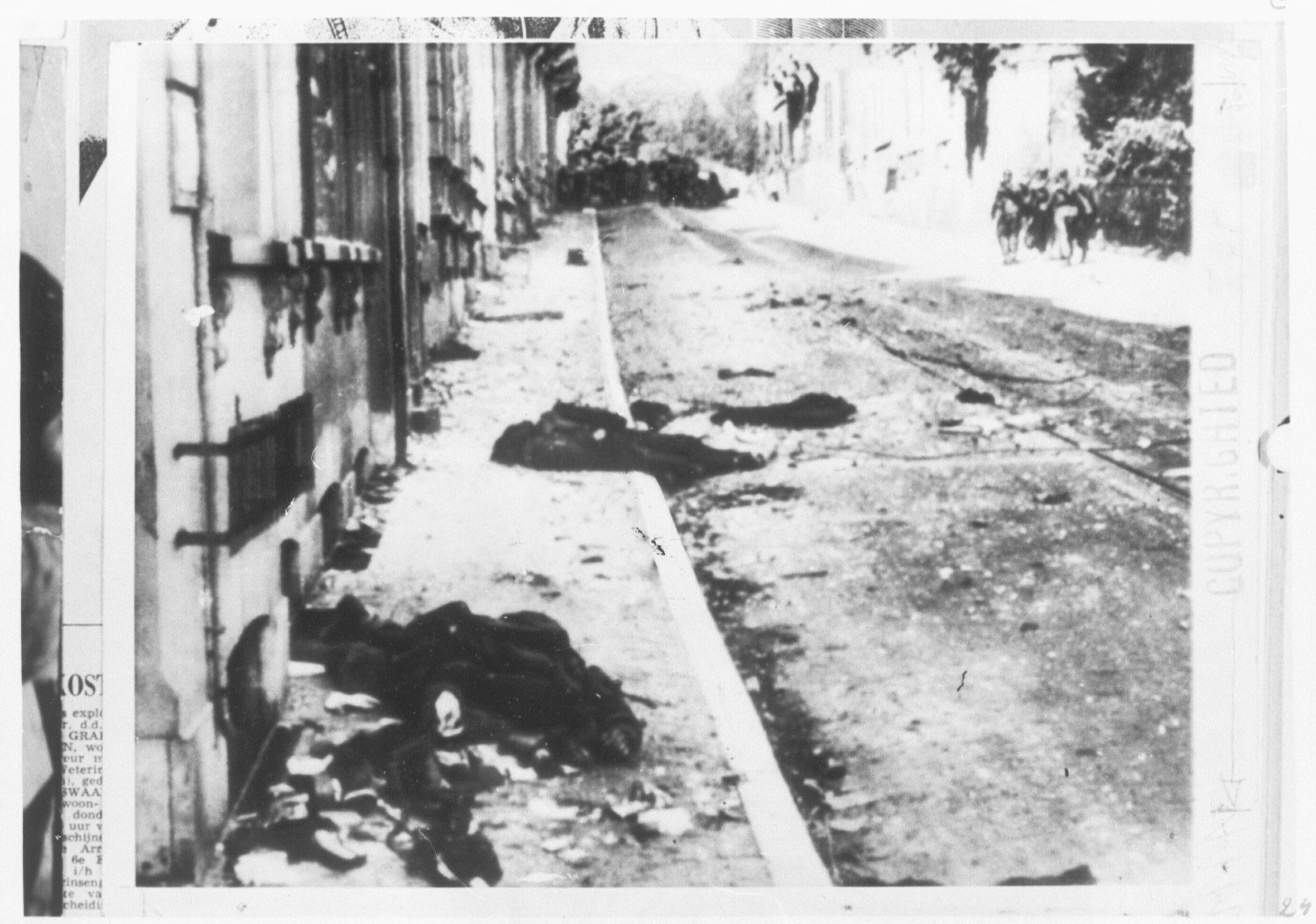 Gesneuvelde Britse militair op de Utrechtseweg in Oosterbeek, met op de achtergrond een Duitse patrouille