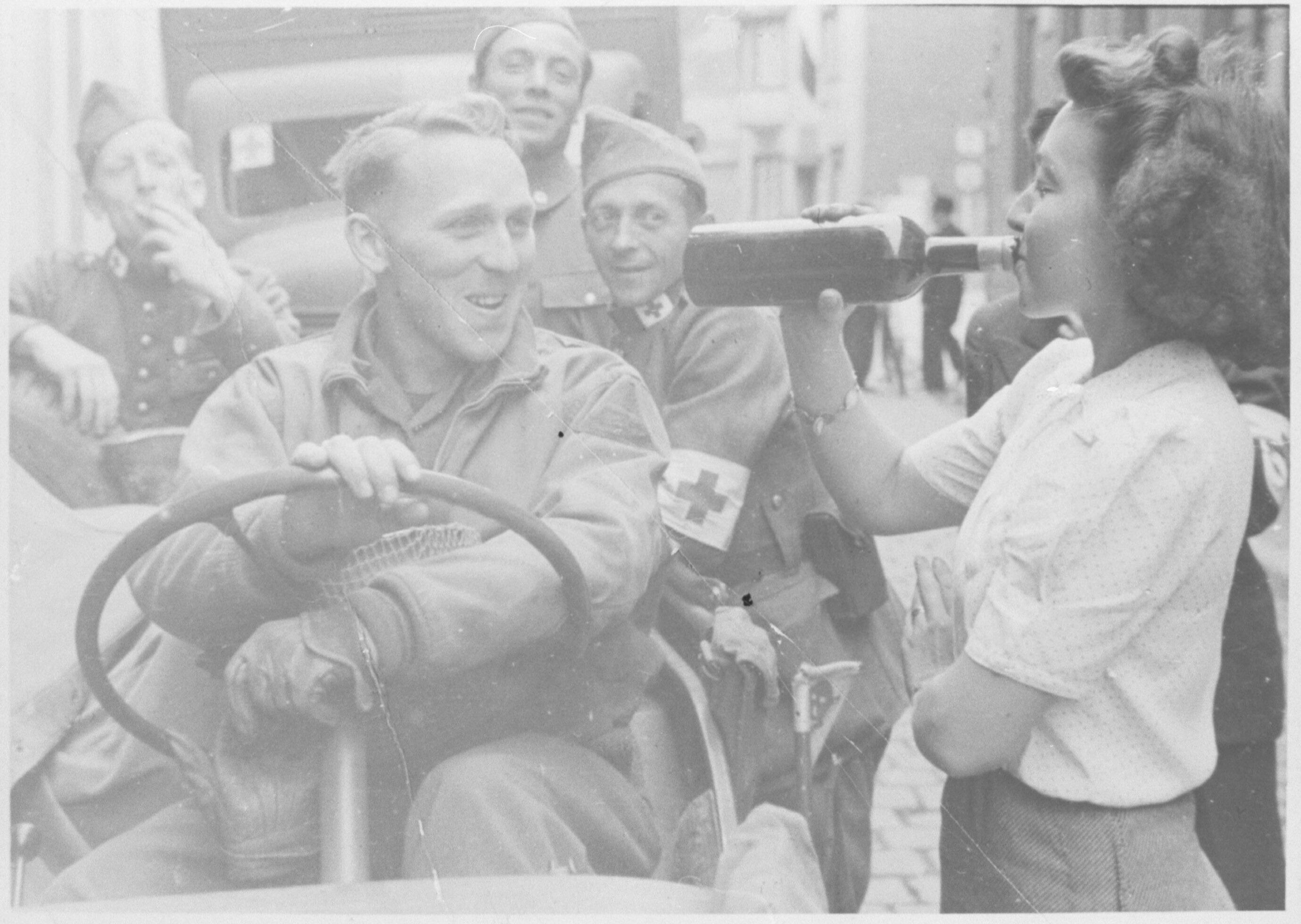 Een vrouw drinkt met geallieerde militairen op de bevrijding.
