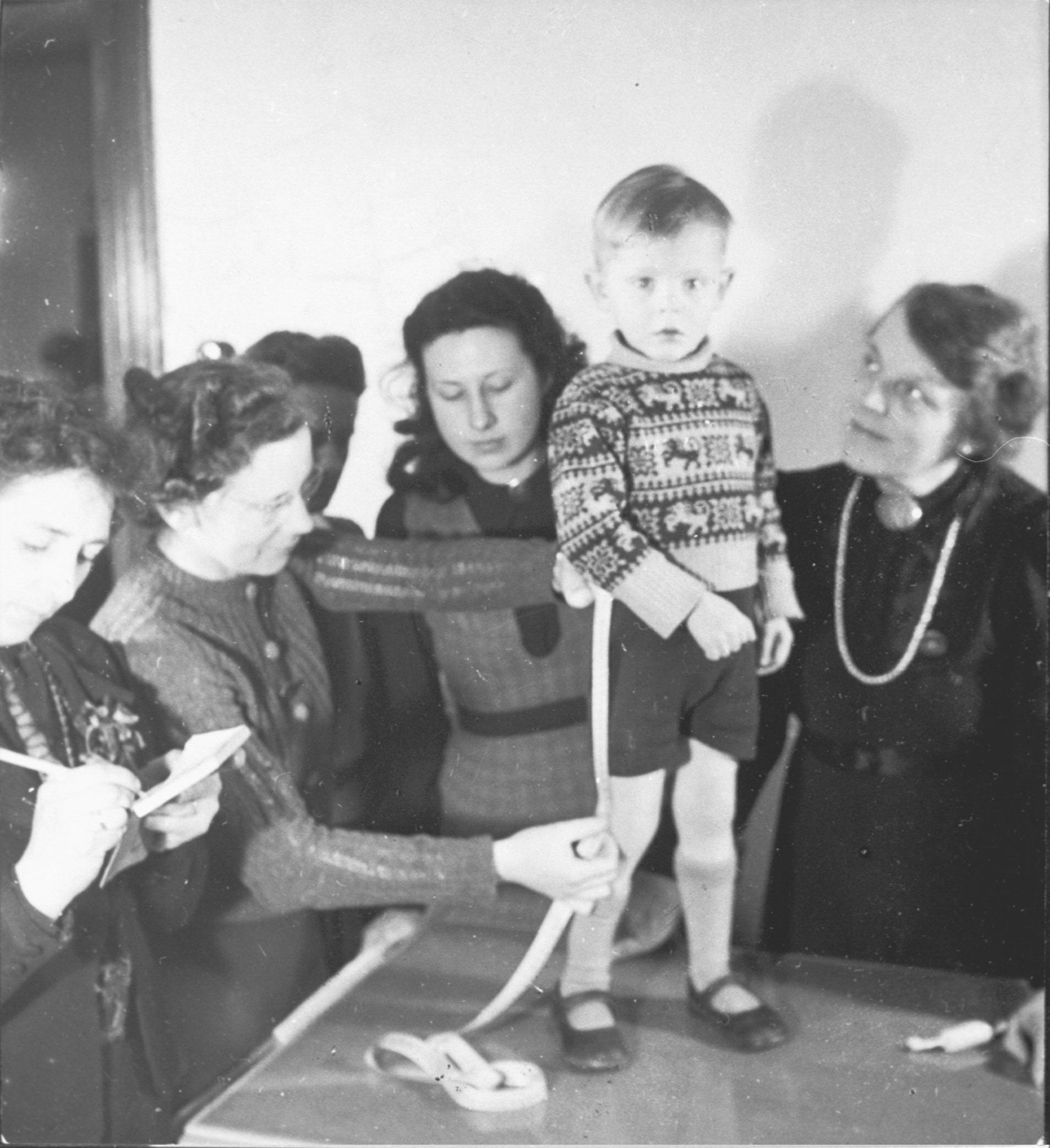 Vrouwen van de NSVO nemen de maat op voor het maken van een korte broek