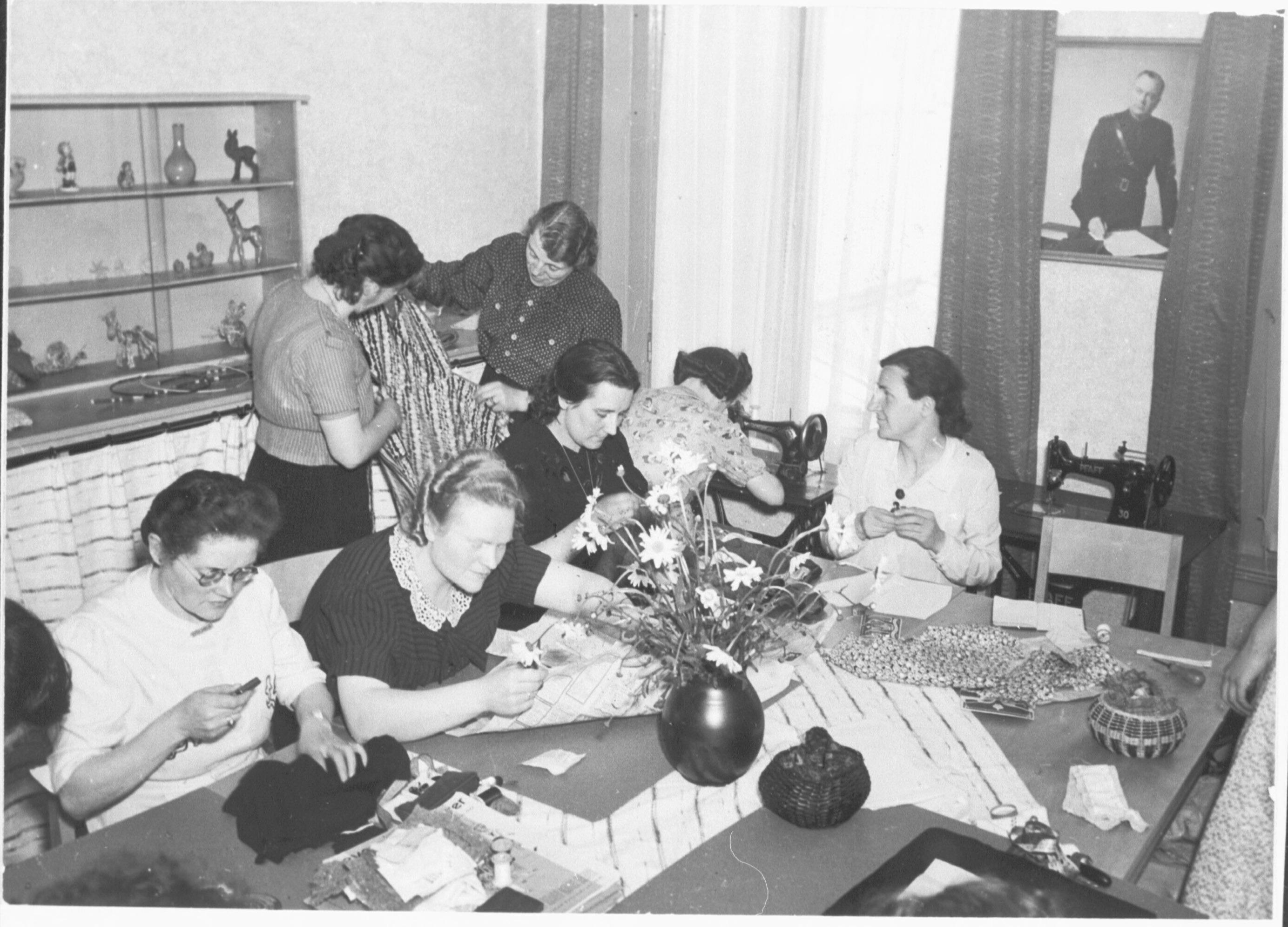 Eerste Moederschool in Arnhem, geopend op 2 mei 1942. Vrouwen tijdens een naai- en verstelmiddag om van oude kledingstukken nieuwe te maken.