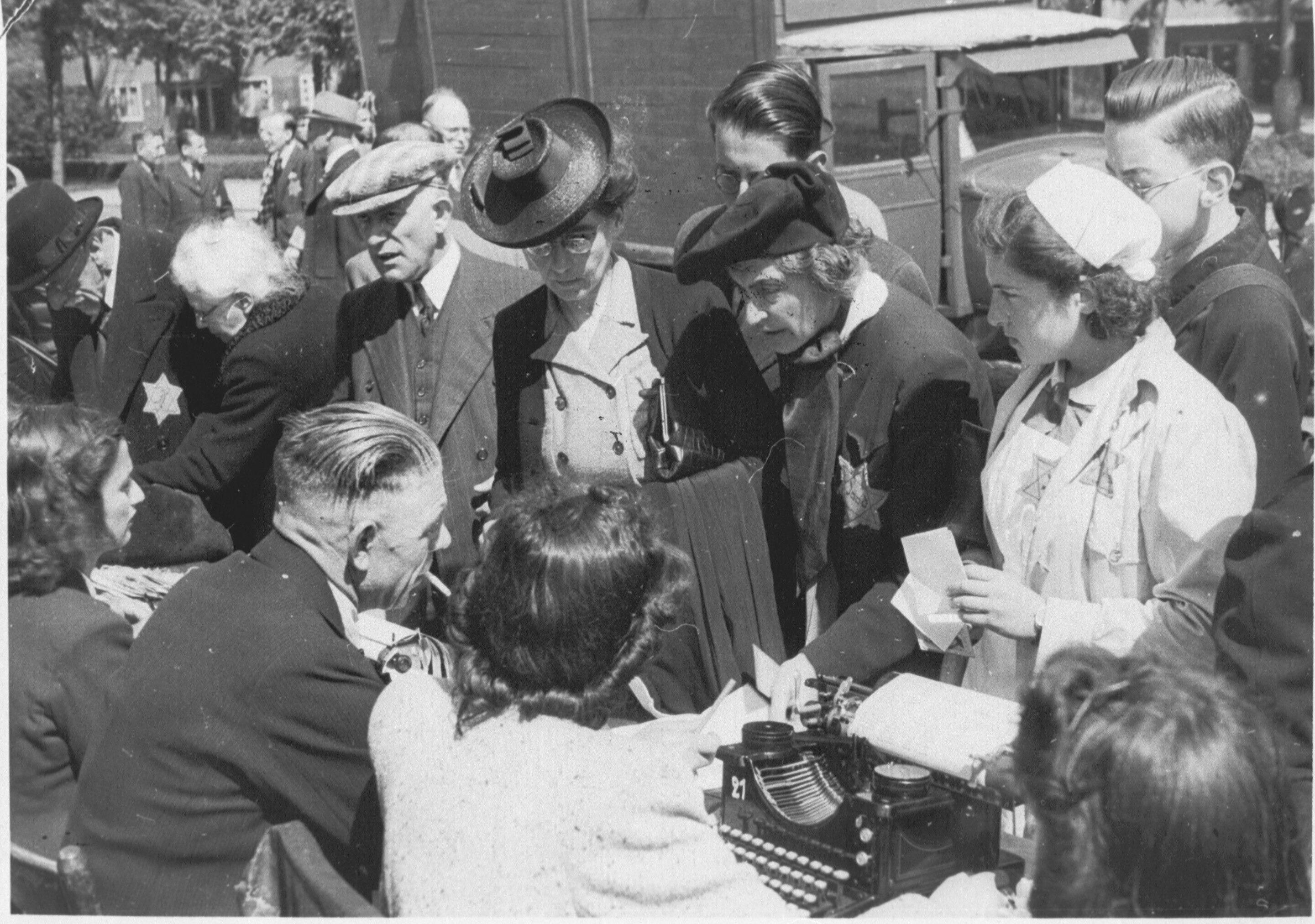 Medewerkers van de kampadministratie van kamp Westerbork schrijven op het Olympiaplein in Amsterdam Joden in op 20 juni 1943