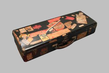 De trompetkoffer met daarop verzamelde etiketten van etenswaren van andere gevangenen die wel pakketen mogen ontvangen