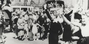 Oorlogsvrijwilligers nemen afscheid op de Dam te Amsterdam voor hun vertrek naar voormalig Nederlands-Indië. De militairen in de vrachtwagens zijn nog in burgerkleding.