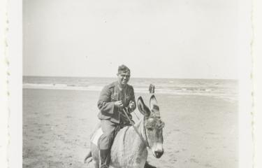 Wehrmacht soldaat rijdt op een ezel aan de Nederlandse kust in 1941